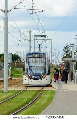 EDINBURGH SCOTLAND - APRIL 16 2016: Passengers waiting to board an Edinburgh tramcar stopped at Gyle Centre station to the west of the city.