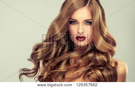 Beautiful girl with long wavy hair .  fair-haired  model  with curly hairstyle   and fashionable makeup . Bright purple lips