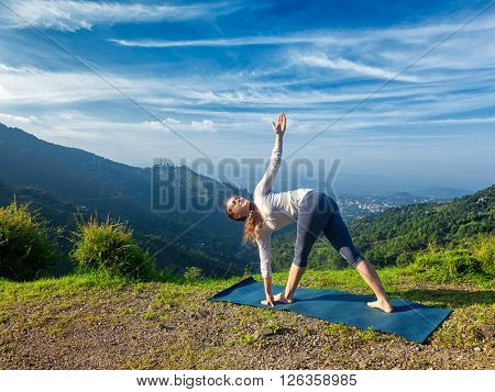 Woman doing Ashtanga Vinyasa yoga asana Parivrtta trikonasana - revolved triangle pose outdoors in mountains in the morning