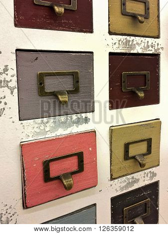 Wooden colorful retro filing cabinet with brass plate