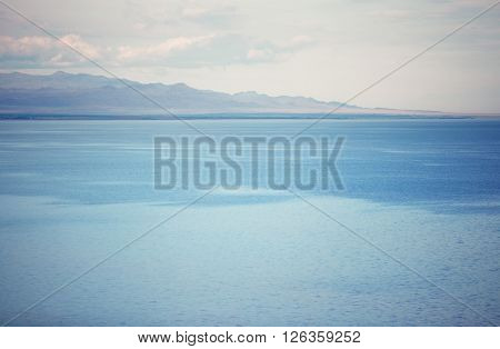 View on the cold lake with mountains on a background