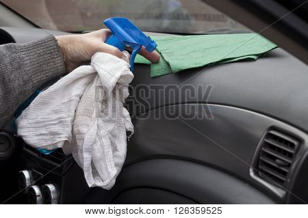 Male hand with rug and car spray cleaning a dashboard outdoor shot with no people