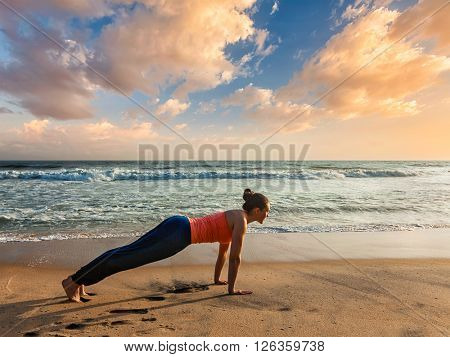 Woman doing Hatha yoga asana Kumbhakasana plank pose  outdoors at beach on sunset. Varkala, Kerala, India