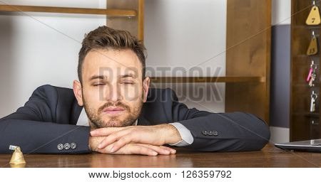 Portrait of a tired receptionist taking a nap at his desk at the hostel reception.