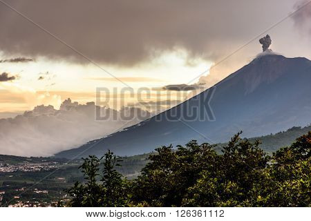 Sunset over active smoking Fuego volcano near Spanish colonial town & UNESCO World Heritage Site of Antigua, Guatemala, Central America