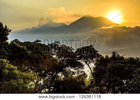 Sun setting over Fuego volcano & Acatenango volcano near Spanish colonial town & UNESCO World Heritage Site of Antigua, Guatemala, Central America