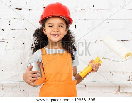 little girl-worker with paint and roller in hands