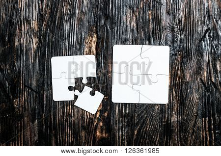 two little white puzzles on dark wooden table top view