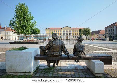 ALBA IULIA, ROMANIA - AUGUST 121, 2015: old woman with veil and child bronze group sculpture in Fortress Square of Carolina Citadel in Alba Iulia, Romania