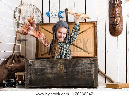 smiling little girl in pilot hat playing wooden plane