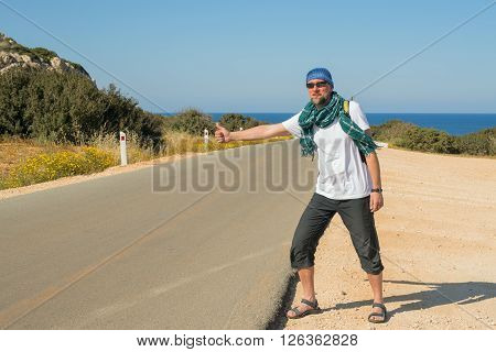 Bearded smiling man with backpack travels hitchhiking alone on the road leading to the sea. Sunny day on the coast.