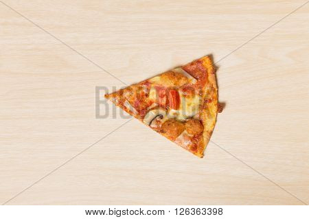 Cut off slice pizza on wood background