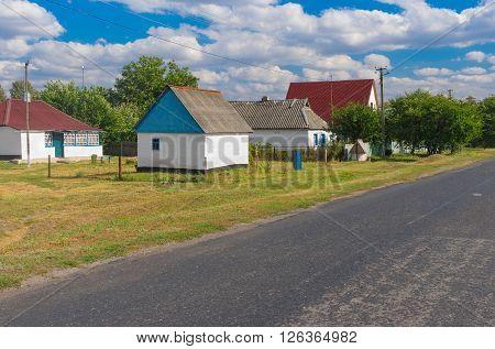 Summer landscape with asphalt road through small remote village Stepanivka in Poltavskaya oblast Ukraine