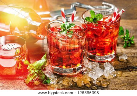 Red drink with strawberry mint leaves ice. Cocktail bar with party lights