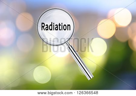 Magnifying lens over background with text Radiation, with the blurred lights visible in the background. 3d Rendering.