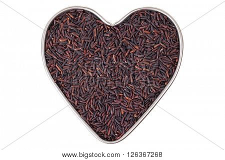 Heart shaped tin pan full of raw Riceberry rice grains in reddish purple shade grown in Thailand, isolated on white background. It is a crossbred between Thai hom nil black and white Jasmine rice