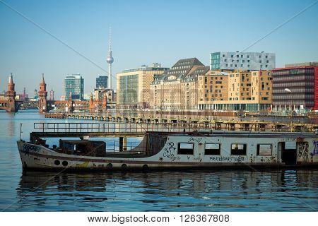 Old abandoned boat with skyline on the Spree in Berlin