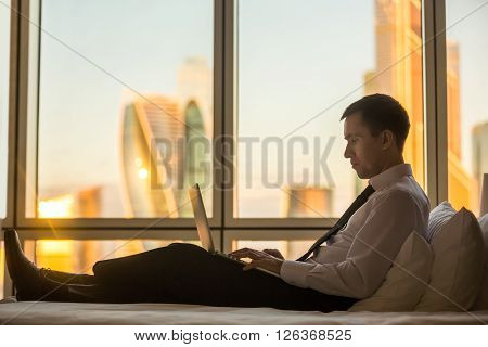 Businessperson working at home or in trip. Side view portrait of handsome young businessman sitting on bed and using laptop. Panoramic window with beautiful dawn city scenery on the background