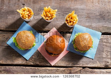Burgers and cups with fries. Fries and burgers on table. Fast food restaurant's morning menu. Delicious vacation snack.