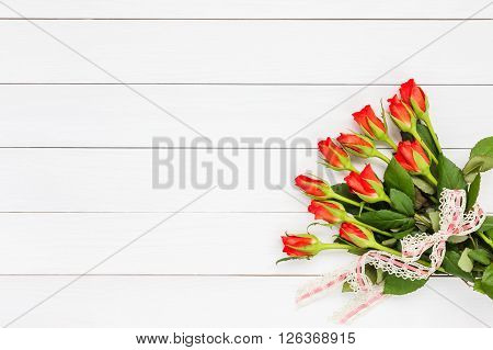 Bouquet Of Red Roses Decorated With Lace On White Wooden Background. Top View, Copy Space