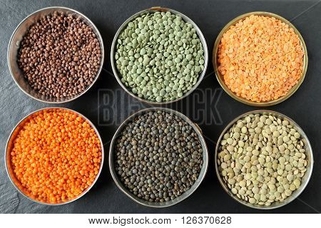 Colorful lentils in metal bowls on a dark background.