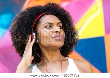 Latin woman listing to music on colorful background