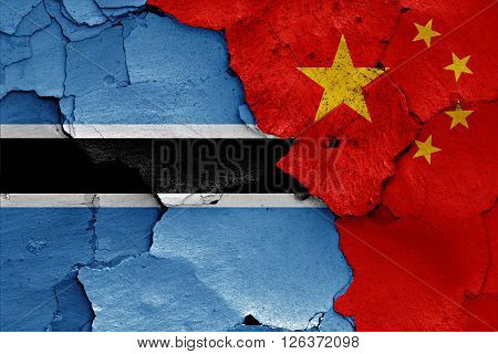 flags of Botswana and China painted on cracked wall