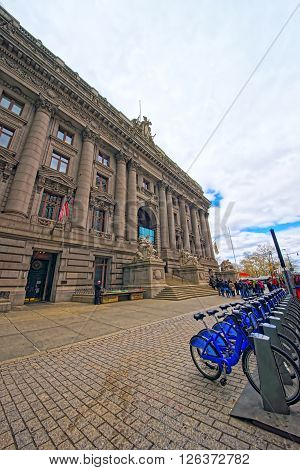 NEW YORK USA - APRIL 24 2015: Alexander Hamilton US Custom House and bicycles Lower Manhattan New York USA. Now it is the National Museum of American Indians. Tourists nearby