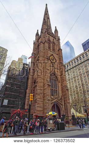 NEW YORK, USA - APRIL 24, 2015: Street view of Trinity Church of Lower Manhattan New York USA. It is a historic parish church near Wall Street and Broadway. Tourists nearby.