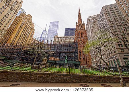 NEW YORK, USA - APRIL 24, 2015: Street view on Trinity Church of Lower Manhattan New York USA. It is a historic parish church near Wall Street and Broadway.