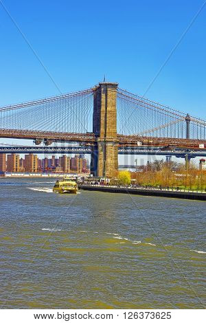 View from Ferry on Brooklyn bridge and Manhattan bridge over East River. Bridges which connect Lower Manhattan with Brooklyn of New York USA. Tourists nearby.