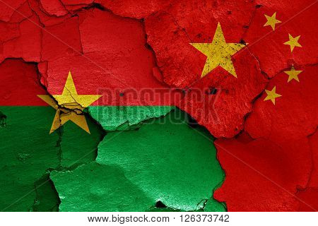 flags of Burkina Faso and China painted on cracked wall