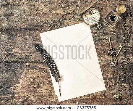 Open book and antique writing accessories. Feather pen and inkwell on wooden background. Vintage toned