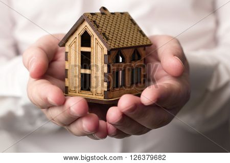 small wooden house in the outstretched hands of men