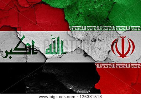 flags of Iraq and Iran painted on cracked wall