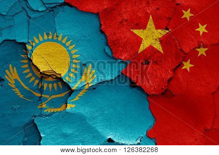 flags of Kazakhstan and China painted on cracked wall