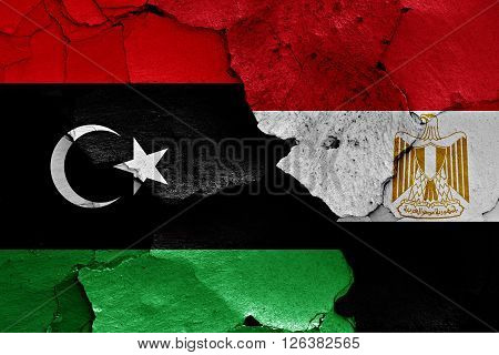 flags of Libya and Egypt painted on cracked wall