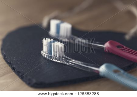 Two new plastic toothbrushes lying on a black mat with focus to the bristles of the blue brush in the foreground in a dental care and healthcare concept