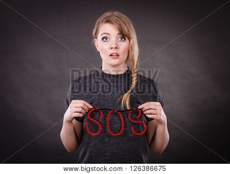 Fear and fright. Young blonde terrified woman needs help. Frightened hopeless female with red sos sign symbol on dark background.
