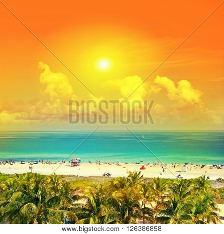 Beautiful sunset. Landscape with blue sky turquoise water and palm trees. Public beach in Miami Beach Ocean Drive