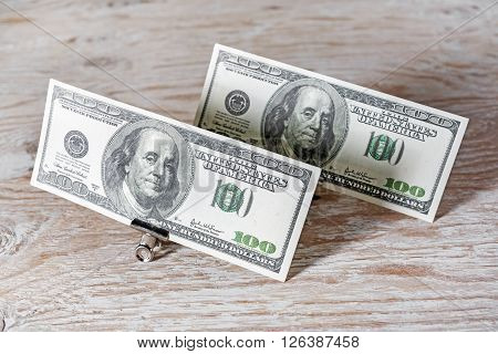 Money in the paper clips.One hundred dollar bills in paper clips standing on a dark wooden background. Fake money.