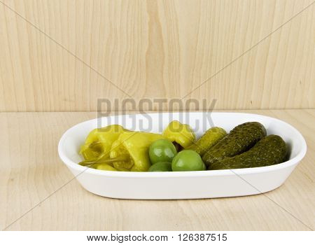 Relish dish of pickles peppers and olives with a wooden display background