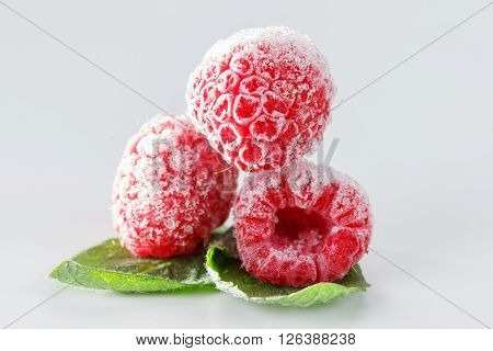 Frozen raspberries macro with mint leaves and ice on white background