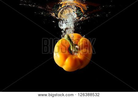 Yellow bulgarian pepper falls into the water isolated on the black background