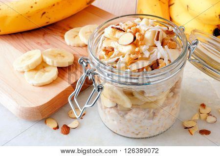 Overnight Oats With Bananas And Nuts In Snap Lid Glass Jar On White Marble