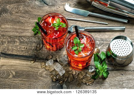 Red cocktail with strawberry mint leaves ice. Drink making bar accessories on wooden table