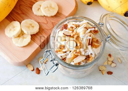 Banana nut overnight oats in glass canning jar on white marble downward view