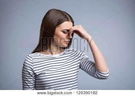 Terrible pain. Pleasant gloomy girl holding her hand on the head and feeling hurt while standing isolated on grey background