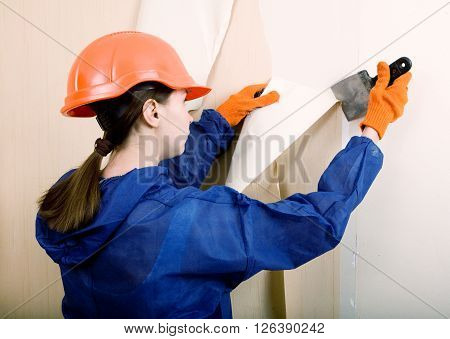 woman worker removes the old wallpaper indoors