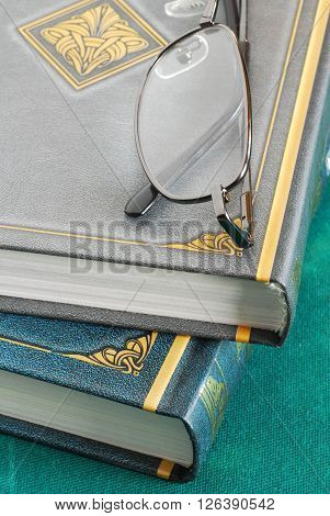 two gray and green books pile with glasses closeup